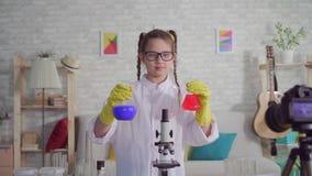 Video blogger för tonårs- flicka i ett vitt lag och skyddsglasögon i labbet som ser le för kamera lager videofilmer