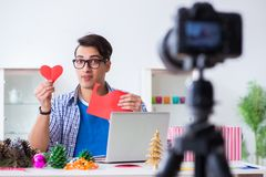 The video blogger recording making paper decoration. Video blogger recording making paper decoration Stock Photo