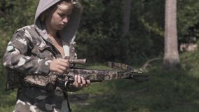 3 in 1 video. blonde in camo jacket is shooting from a crossbow slow motion