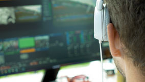 Video broadcast editor with headphones at screen Stock Image