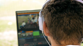 Video broadcast editor with headphones at screen Royalty Free Stock Images