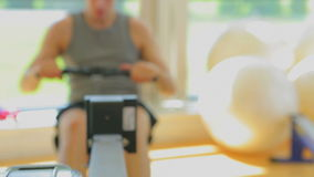 Video of brunette man using the row machine Royalty Free Stock Photos