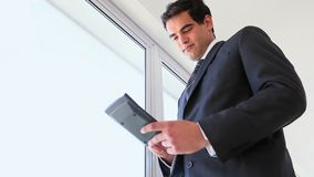Video of a businessman using a calculator. While standing stock footage
