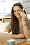 Video call. Young woman having video call, using laptop and headset, smiling royalty free stock photography