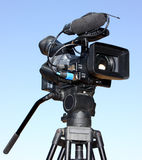 A video camera. A digital video camera on tripod isolated on a clear blue sky background royalty free stock photos
