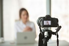 Video camera filming live training of successful business coach. Professional video camera recording successful businesswoman giving online training or filming royalty free stock photography