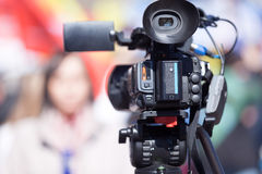 Video camera in the focus, blurred female reporter in the background Stock Image