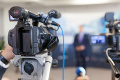 Video camera in focus, blurred spokesman in background. Video camera in focus, blurred spokesperson in background. Corporate news conference Royalty Free Stock Images