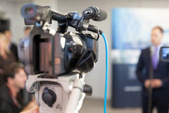 Video camera in focus, blurred spokesperson in background. Video camera in focus, blurred spokesman in background. Corporate news conference Stock Photography