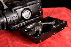 Video camera and a hard disk. On a red blanket Royalty Free Stock Photos
