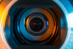 Video camera lens. Closeup lit in orange and blue royalty free stock photo