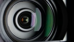 Video camera lens, showing zoom and glare, come to. Black video camera lens, turns and showing zoom and glare, photocamera or videocamera, come to the shadow and stock video footage