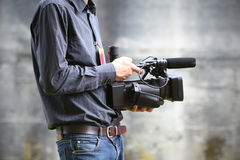 Video camera man with camera. On gray background Stock Photo