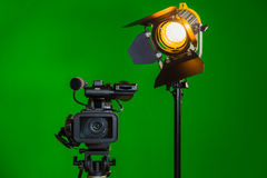 A video camera and a spotlight with a Fresnel lens on a green background. Filming in the interior. The chroma key Stock Photos