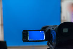 Video camera in a studio focused on blue background Royalty Free Stock Photos