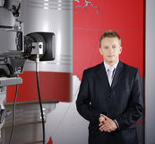 Video camera and television reporter. Close up of blond middle age television news presenter in studio in front of the camera Stock Photography