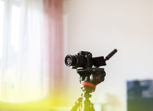 Video camera on tripod used by vlogger influencer for video chan. Video camera on tripod in home environment - modern technology used by influencer vlogger for Stock Photos
