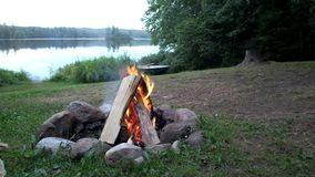 Fire camp beside a lake daytime. Video of Camp fire with moutain and lake view ,nice nature scene at sunset stock footage