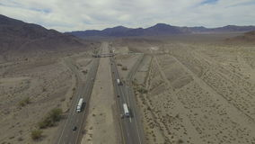 Video of cars driving along a desert road. Birdseye view of cars driving along a desert road in the daytime stock footage
