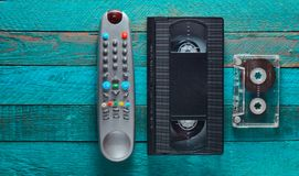 Video cassette, audio cassette, remote control on a turquoise wooden table. Retro media technology from the 80s. Copy space. Top v. Video cassette, audio stock images