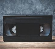 Video cassette close-up on a wooden shelf. Against a gray concrete wall. Retro technology for watching videos royalty free stock photos