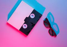 Video cassette in cover, 3D glasses. 80s. Retro wave, blue red neon light, ultraviolet. Top view, minimalism stock image