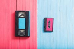 Video cassette and tape cassette on pink and blue background. Video cassette and tape cassette on pink and blue wooden background background. Retro concept royalty free stock photos