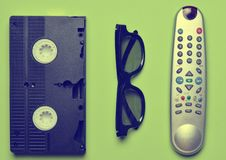 Video cassette, TV remote, 3d glasses on a green. Pastel background. Entertainment 90s. Top view. Flat lay stock photo