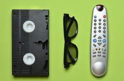Video cassette, TV remote, 3d glasses on a green pastel background. Entertainment 90s. Top view. Flat lay Stock Image