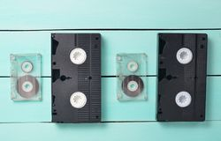 Video cassettes and audio cassettes on a turquoise wooden table. Retro video and audio technology. stock photography