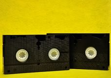 Video cassettes. Isolated on a yellow background royalty free stock photo