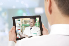 Video chat with doctor. Man having video chat with doctor on laptop at home Stock Photo
