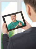 Video chat with doctor. Man having video chat with doctor on laptop at home Stock Image