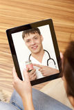 Video chat with doctor. Woman having video chat with doctor on laptop at home Stock Photography