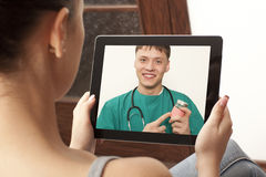 Video chat with doctor. Woman having video chat with doctor on laptop at home Stock Photos