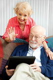 Video Chat with the Grandkids. Senior couple doing a video chat with their grandchildren using their tablet PC Stock Photo