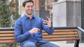 Video Chat on Smartphone by Young Man Sitting Outdoor. 4k high quality, 4k high quality stock footage