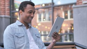 Video Chat on Tablet by African Man Sitting Outdoor. 4k high quality, 4k high quality stock footage