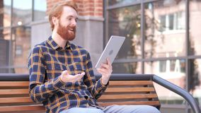 Video Chat on Tablet by Redhead Beard Young Man Sitting on Bench stock video