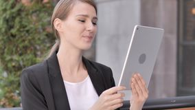Video Chat on Tablet by Young Businesswoman Sitting Outdoor. 4k high quality, 4k high quality stock footage