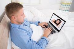 Video chiacchierata dell'uomo con la donna a casa fotografia stock