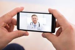 Video chiacchierata dell'uomo con medico immagini stock