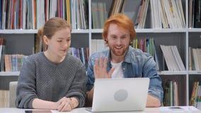 Video chiacchierata online dalle coppie, compagni di squadra sul computer portatile in ufficio fotografia stock libera da diritti