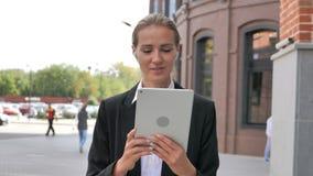 Video chiacchierata online sulla compressa dalla donna di affari di camminata stock footage