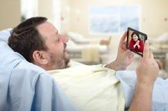 Video chiacchierata sul letto di ospedale con il telefono cellulare Fotografie Stock Libere da Diritti