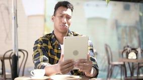 Video chiacchierata sulla compressa dal giovane uomo africano, caffè all'aperto stock footage