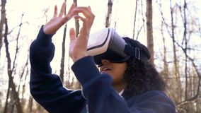 African American girl teenager female young woman using virtual reality VR headset in a forest woodland environment stock footage