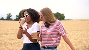 Teenagers young women wearing sunglasses drinking coffee and using their smart phones for social media. Video clip of pretty blonde girl and mixed race teenager stock footage