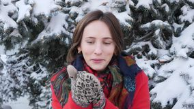 This video is about Close up Beautiful young brunette woman in red coat, scarf, mittens,  smiling freezing trying to warm up, blow. Ing on hands outside on stock video