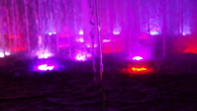 Video close up shot of a fountain water feature clear water line and jets with changing colour LED light stock video